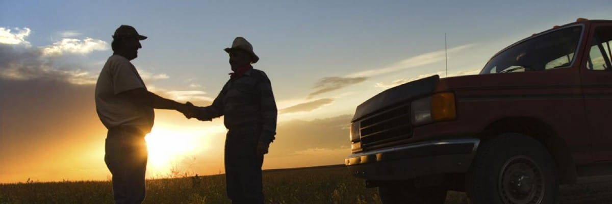 ranchers shaking hands by a pickup truck
